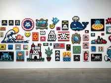"Wall of aliases by Invader at ""Into the White Cube"""